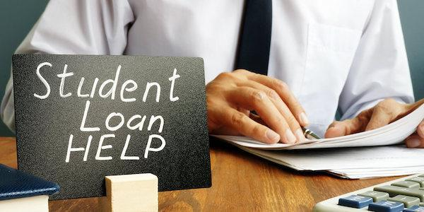 "A sign reading ""Student Loan Help"" in front of a person looking at paperwork."